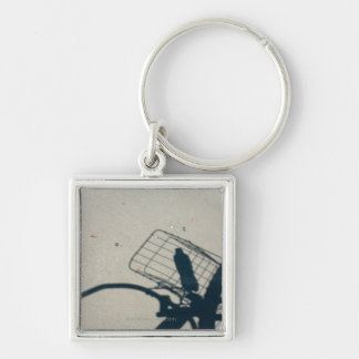 The shadow of a bicycle with a bottle of water Silver-Colored square key ring