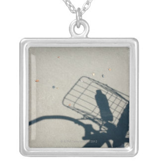 The shadow of a bicycle with a bottle of water silver plated necklace