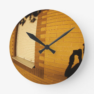 The shadow of a man on the illuminated wall of a h wall clock