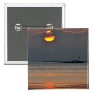 The sun emerges through an off-shore fog bank 15 cm square badge