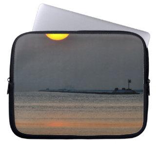 The sun emerges through an off-shore fog bank laptop sleeve