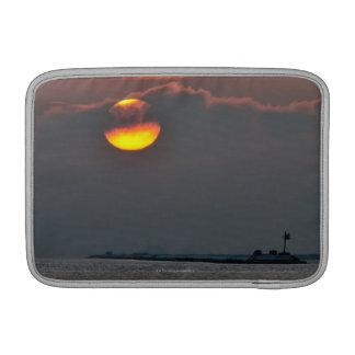The sun emerges through an off-shore fog bank MacBook sleeves
