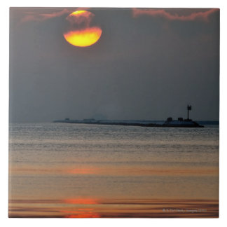 The sun emerges through an off-shore fog bank large square tile
