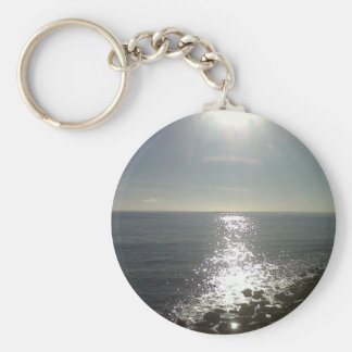 the sun rising over the sea key ring