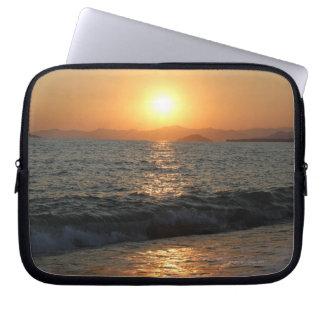 The sun sets over a beautiful mountain range, laptop sleeve