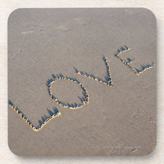 The word Love spelled out in the sand. Drink Coasters
