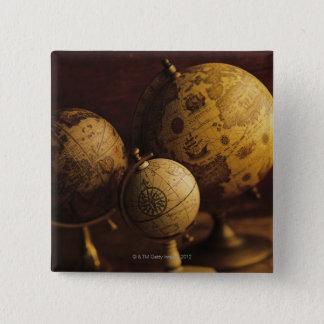 Three antique globes 15 cm square badge