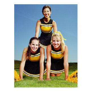 Three cheerleaders forming human pyramid on postcard