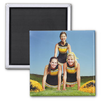 Three cheerleaders forming human pyramid on square magnet