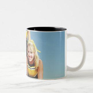 Three cheerleaders forming human pyramid on Two-Tone coffee mug
