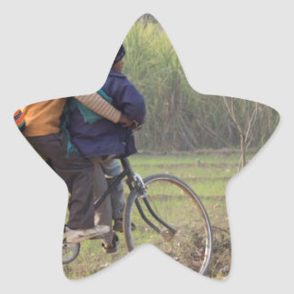 Three children on a cycle at the side of the road star sticker