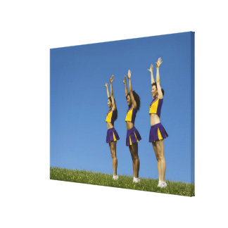 Three female cheerleaders standing in row canvas print