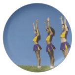 Three female cheerleaders standing in row dinner plate