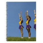 Three female cheerleaders standing in row spiral notebook