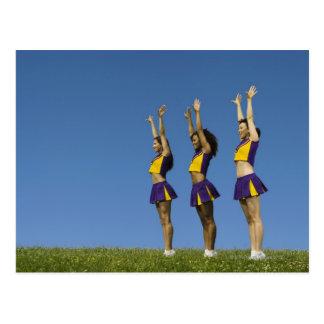 Three female cheerleaders standing in row postcard