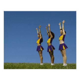 Three female cheerleaders standing in row poster