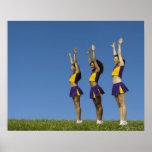 Three female cheerleaders standing in row posters