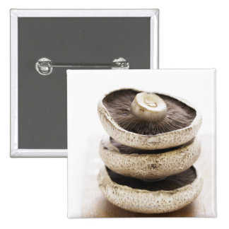Three flat mushrooms in pile on wooden board 15 cm square badge