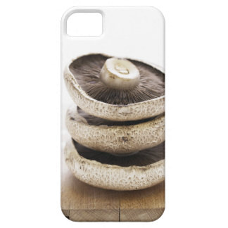 Three flat mushrooms in pile on wooden board, iPhone 5 cases