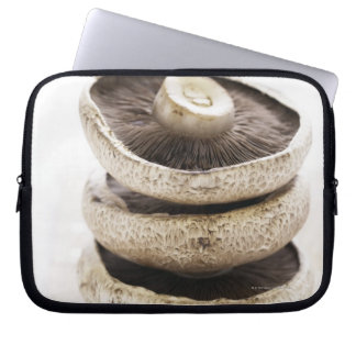 Three flat mushrooms in pile on wooden board, laptop sleeve