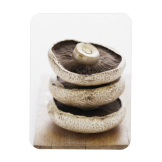 Three flat mushrooms in pile on wooden board, magnet