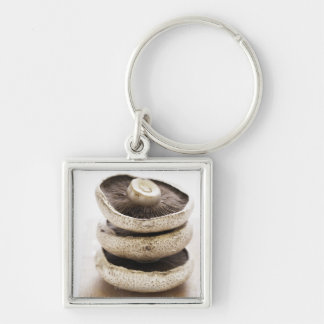 Three flat mushrooms in pile on wooden board, Silver-Colored square key ring