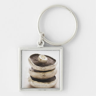 Three flat mushrooms in pile on wooden board Silver-Colored square key ring