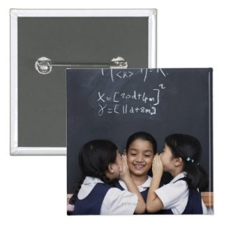 Three girls in classroom whispering 15 cm square badge