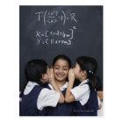 Three girls in classroom whispering postcard