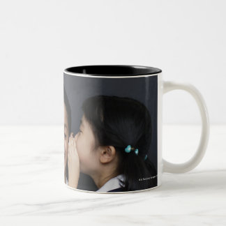 Three girls in classroom whispering Two-Tone coffee mug