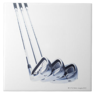 Three golf clubs on white background tile