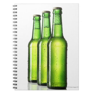 Three green bottles of beer on white background, notebook