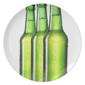Three green bottles of beer on white background, plate