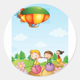 Three kids playing below an airship round sticker