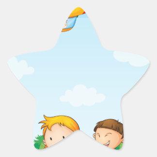 Three kids playing below an airship star sticker