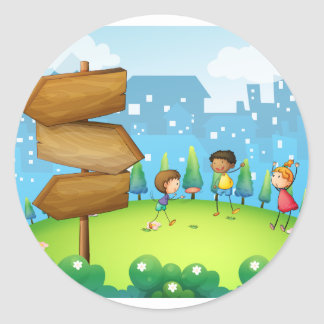 Three kids playing in the hill with wooden arrowbo round sticker