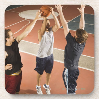 three men in athletic clothing playing coaster