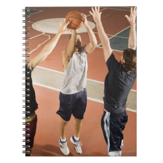 three men in athletic clothing playing spiral notebook