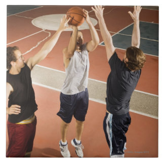 three men in athletic clothing playing large square tile