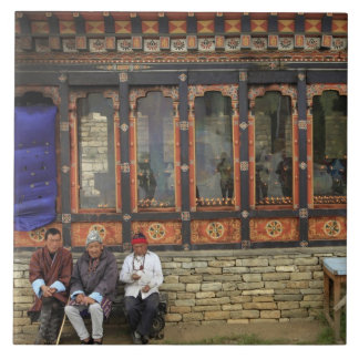 Three men sit on a bench at the Memorial Chorten Tile
