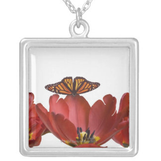 Three red tulips and a monarch butterfly against silver plated necklace