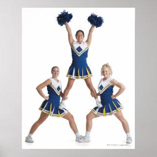 three teenage caucasian female cheerleaders in poster