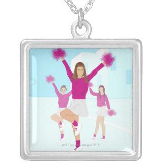 Three teenage cheerleaders holding pom poms 2 necklaces