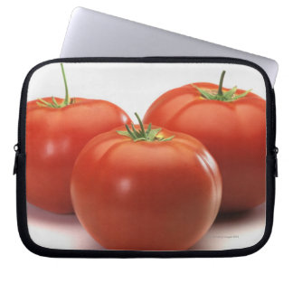 Three tomatoes on counter, close-up laptop sleeve