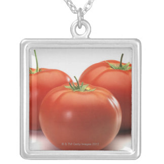 Three tomatoes on counter, close-up silver plated necklace