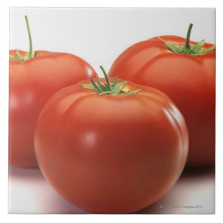 Three tomatoes on counter, close-up tile