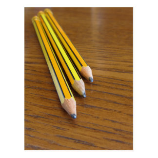 Three used pencils on wooden table postcard