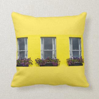 Three windows on a yellow wall cushion