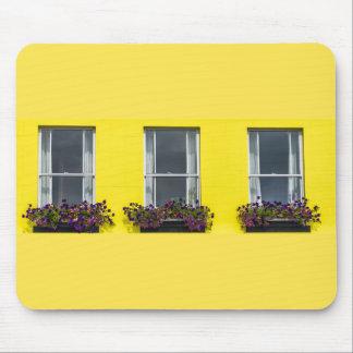 Three windows on a yellow wall mousepad