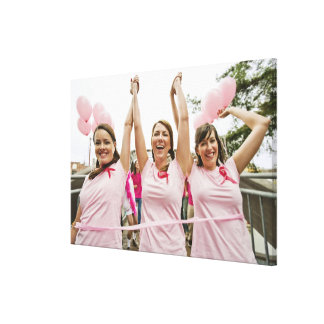 Three young women dressed in pink run in canvas print